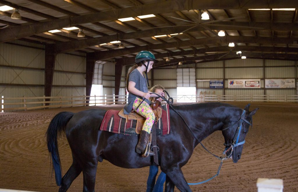 Young girl rides a horse in a covered arena. Horseback riding teaches important life lessons. Mommy blog, lifestyle blogger.
