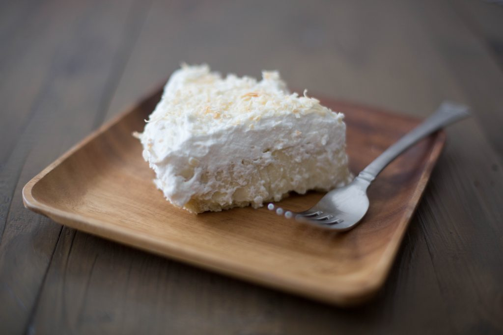 Slice of old fashioned coconut cream pie with toasted coconut on bamboo plate. Mommy blogger lifestyle blog