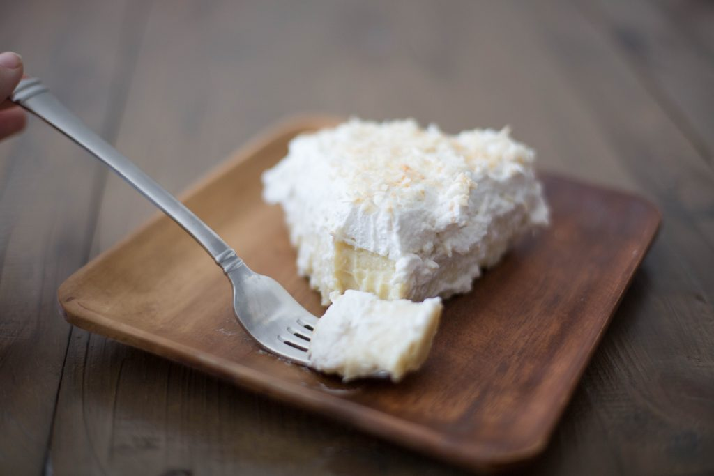 Delicious bite of old fashioned coconut cream pie on bamboo plate