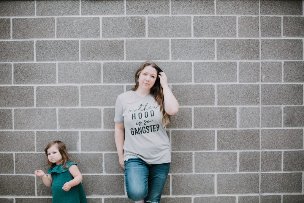 Woman wearing a motherhood is so gangster t shirt leaning against a wall with her toddler daughter. Mommy blogger lifestyle blog mom blog