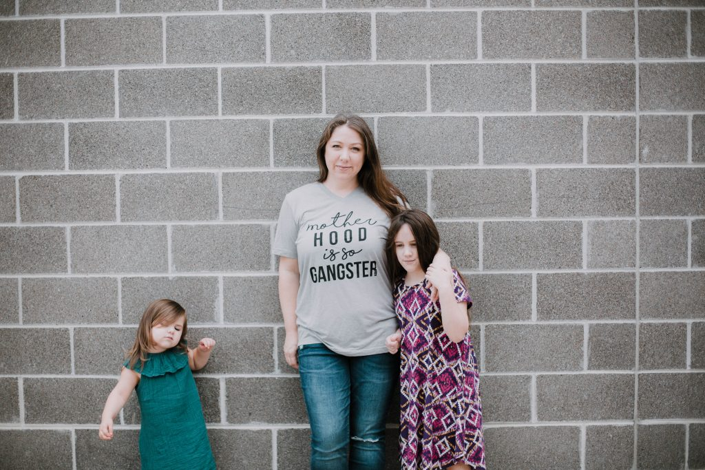 Woman wearing a motherhood is so gangster t shirt leaning against a wall with her school age and toddler daughters. Mommy blogger lifestyle blog mom blog