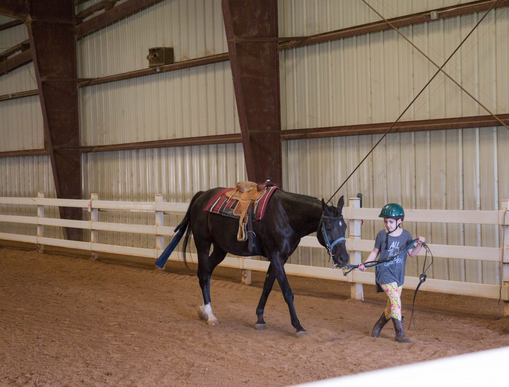 Working hard during horseback lessons teaches responsibility and character. Little girl leading a horse out of the arena. Mommy blog, lifestyle blogger.