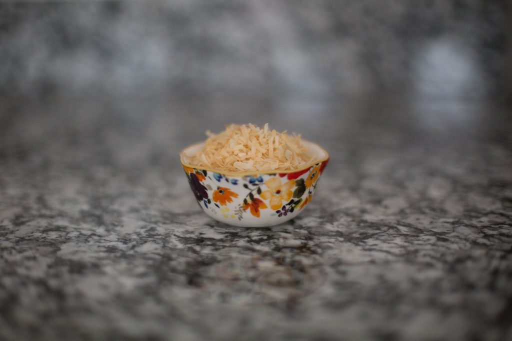 Golden brown toasted coconut flakes for old fashioned coconut cream pie in a beautiful Pioneer Woman measuring cup. Mommy blogger lifestyle blog