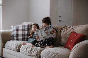 Four favorite Christmas books that we read all year long. Funny touching books for christmas time. Reading books mom blogger lifestyle blog mommy blog 2017 2018 Sisters sitting on the couch reading and laughing together