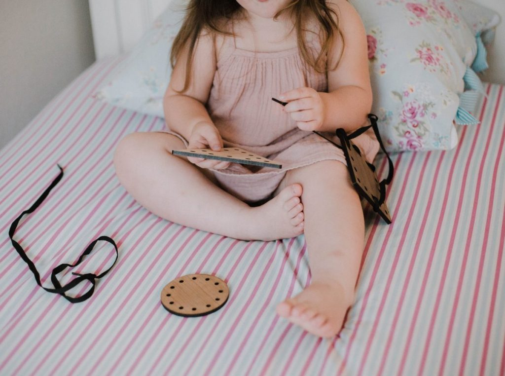 little girl excited to play with a wooden lacing puzzle toy fine motor skills eco friendly toys non toxic wooden toys houston blogger mommy blogger mom blog lifestyle blogger 2018