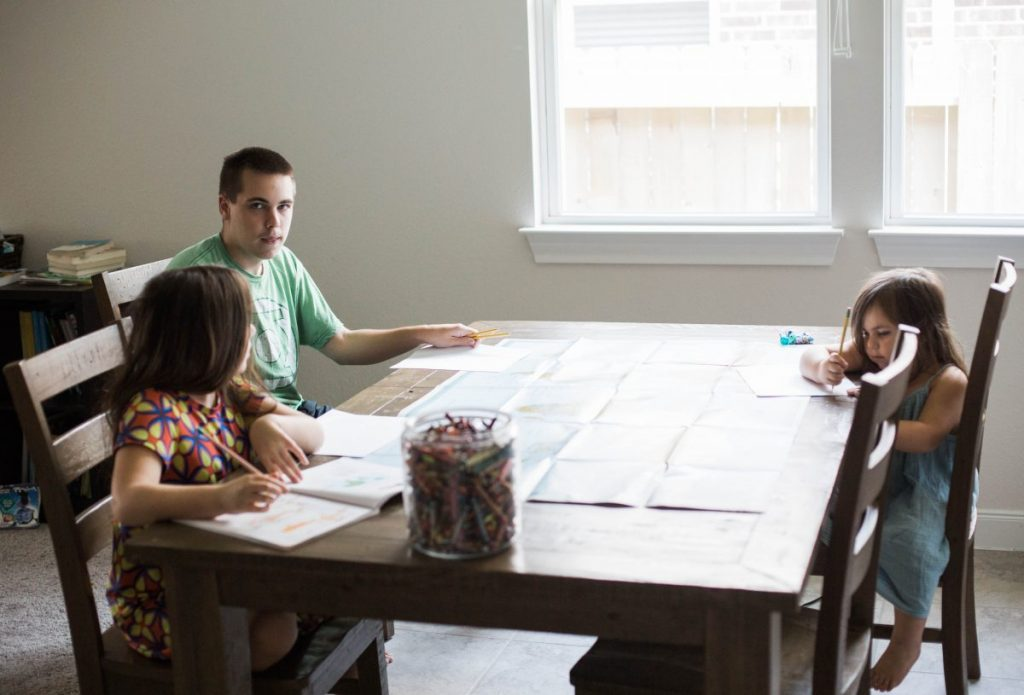 Learning together in homeschool using one-pagers. Three kids at the table drawing and writing facts. Unschooling is how we learn. Houston lifestyle and parenting blogger, 2018.