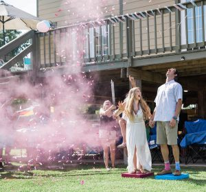Creative gender reveal excitement and joy. It's a girl pink confetti cannons.