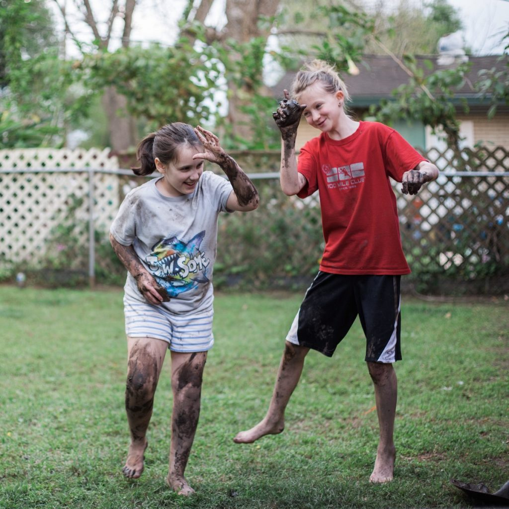 Two smiling girls covered in mud and doing silly Fortnite dances