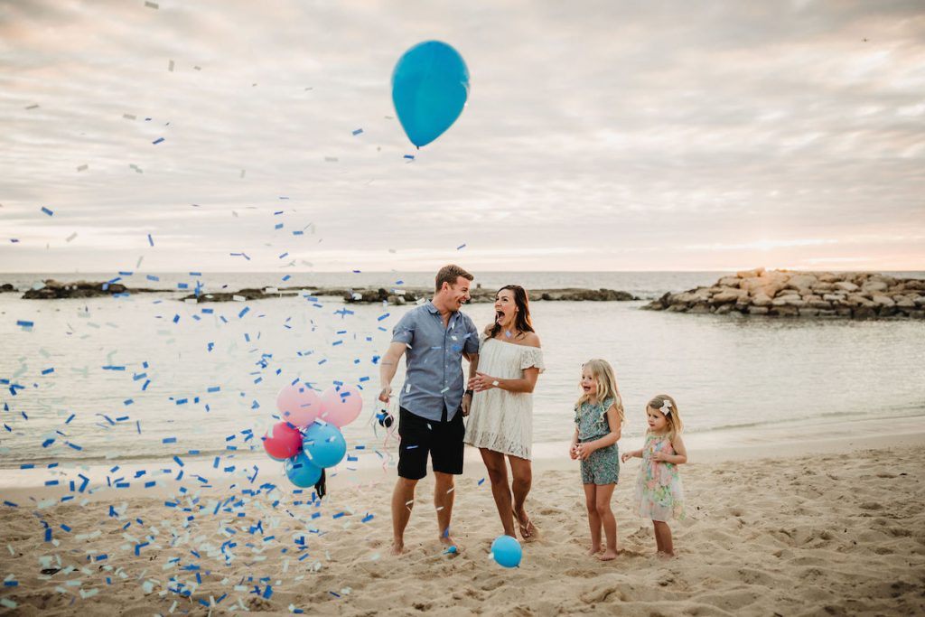 Creative balloon and confetti baby boy gender reveal on the beach